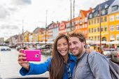 Copenhagen travel couple tourists taking selfie photo with phone camera. Smiling young people studen poster