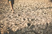 Feet Of Boy Walking On Cracked Dry Ground .concept Hope And Drought poster