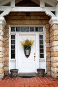 picture of front door  - White door with transom and side lights on stone house with flower basket - JPG