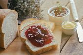 Delicious Toast Bread Served With Butter And Spread With Strawberry Jam On Wood Cutting Board Put On poster