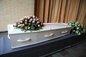 stock photo of coffin  - A whtie coffin with pink flowers at a funeral service - JPG