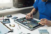 Computer Repairman Installing New Hard Disk Drive In Laptop poster