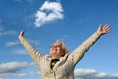 stock photo of grandma  - Image of an excited old woman with her arms raised up in the air as she smiled to the sky in pride - JPG