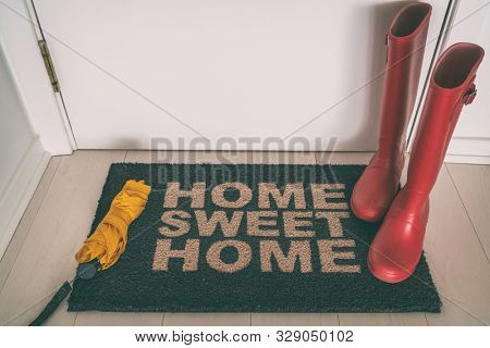 poster of Autumn rain boots on entrance door mat at front of house with wet umbrella welcome rug on wooden flo
