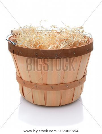 Bushel basket with a wood handle and stuffed with straw over a white background and slight reflection.