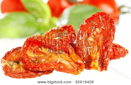 sun-dried tomatoes with basil leaves and tomato on background, over  white