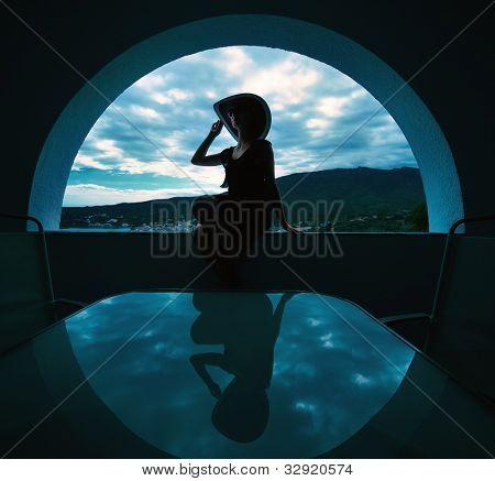 Woman's silhouette in window opening.