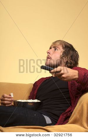 Young Man Watching TV and Eating Popcorn
