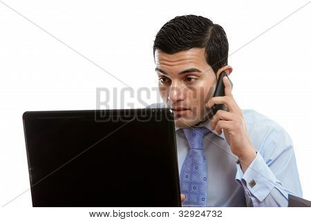 Man At Computer Making Or Receiving Phone Call