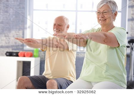 Mature people exercising happily in the gym.