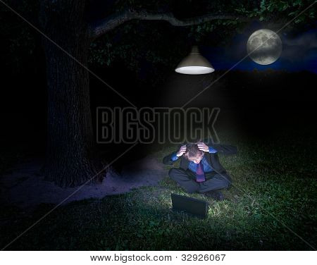 Frustrated young man with laptop in forest