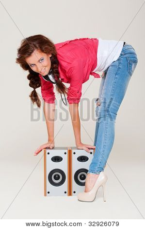studio shot of smiley woman with speakers over grey background
