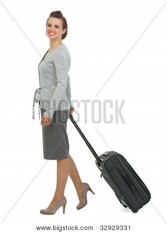 Happy Traveling Woman With Suitcase Walking Sideways