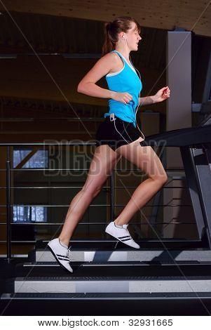 beautiful woman is running on the treadmill