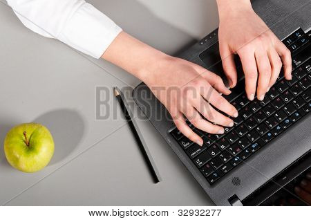 female hands are working on modern laptop, view from above