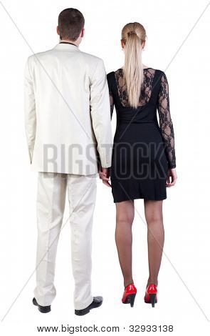 Back view of  business team look into the distance.  beautiful friendly girl in dress and guy in suit together. Rear view people collection.  backside view of person.  Isolated over white background.