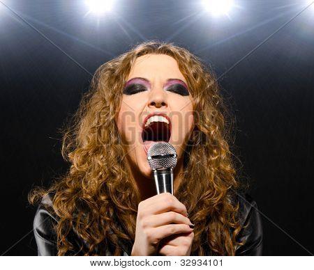 Frau ist Rock-Song mit einem Mikrofon singen.
