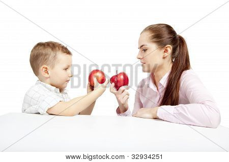 A child, woman and apples.