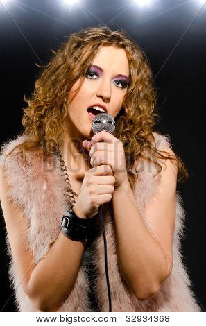 woman is singing glam rock song with a microphone