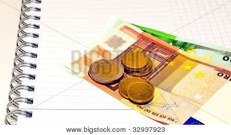 euro notes and coins on the note book