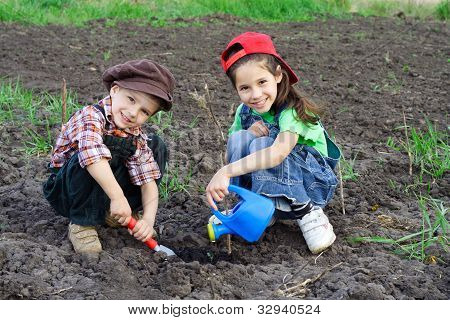 Two kids watering the sprout