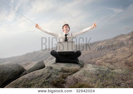 Young businessman sitting on a rock and triumphing with a laptop on his knees