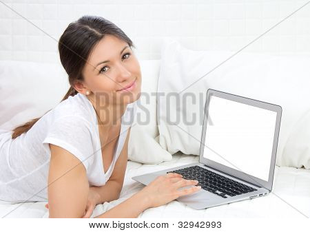 Woman Lying On The Sofa With Modern Laptop