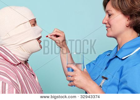 Photo of a nurse giving a patient some medicine in the form of a pill.