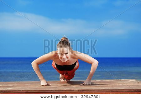 Young beautiful woman doing fitness exercises at the beach