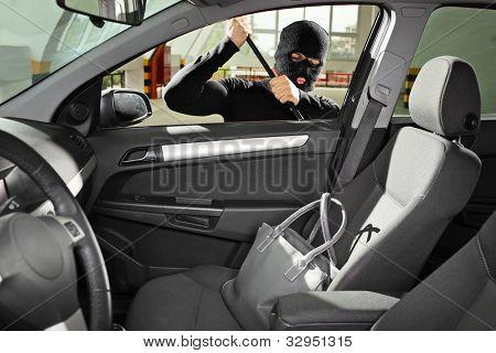 Um ladrão usando uma máscara de roubo tentando roubar um saco de bolsa em um automóvel