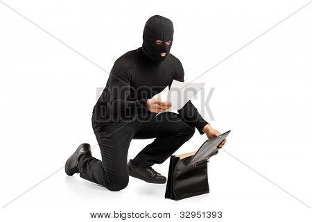 ein Dieb lesen eine vertrauliche Dokumente nach Diebstahl einer Aktentasche isoliert auf weißem Hintergrund