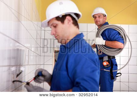 Electricians plumbing a bathroom