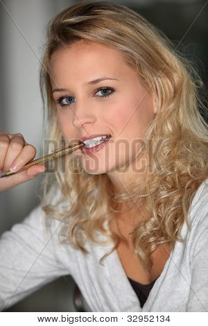 Woman with a pen in her mouth