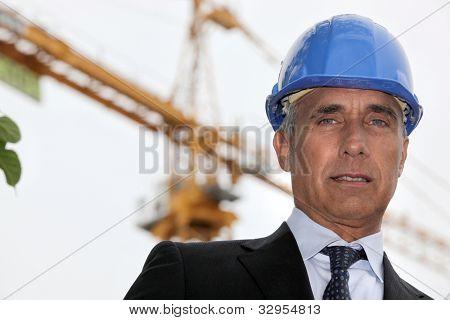 Senior building planner stood on construction site