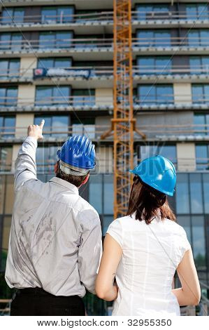 Construction Engineer Pointing On An Area Of The Building On Construction Site