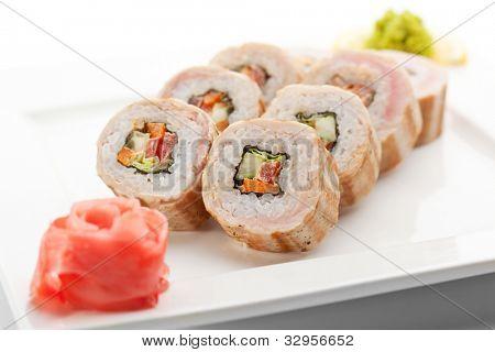 Rollen Sie Maki-Sushi - aus Gurke, Paprika, Salat im Inneren. Speck außerhalb