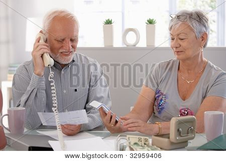 Elderly couple checking bills at home, discussing finances.