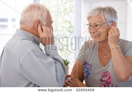 Elderly couple listening to music on mp3 player, smiling.