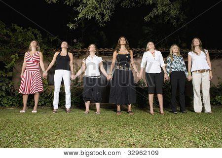 Hispanic women holding hands in a row