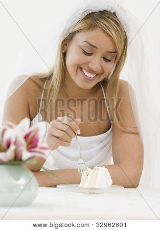 Hispanic bride eating cake