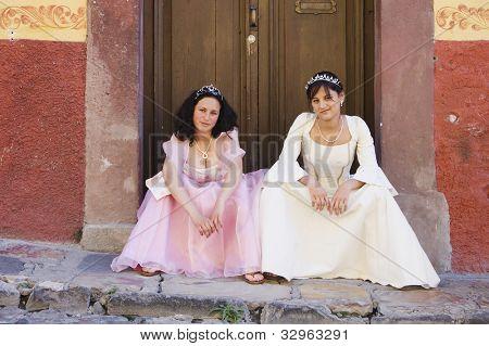 Hispanic girls wearing Quinceanera dresses