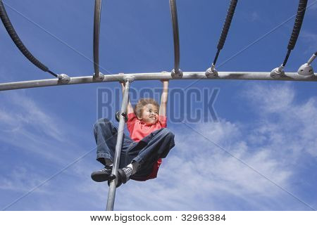 African American boy playing on jungle gym