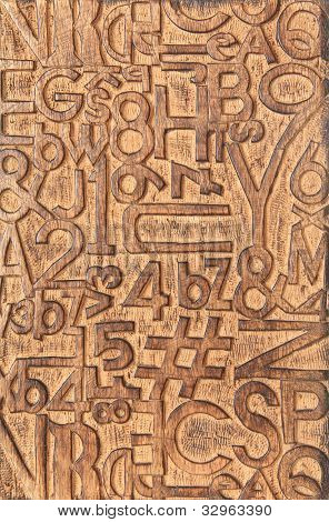 Letters and numbers carved into a wooden block.