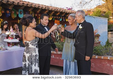 Hispanic couples toasting at Quinceanera