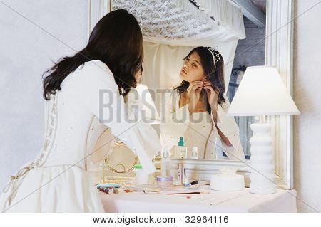 Hispanic girl putting on earring in Quinceanera dress