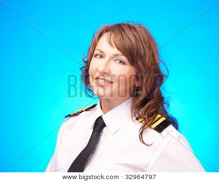 Beautiful woman pilot wearing uniform with epauletes standing on blue background.