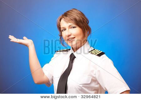 Beautiful woman pilot wearing uniform with epaulettes, presenting something on her hand, standing on blue background.