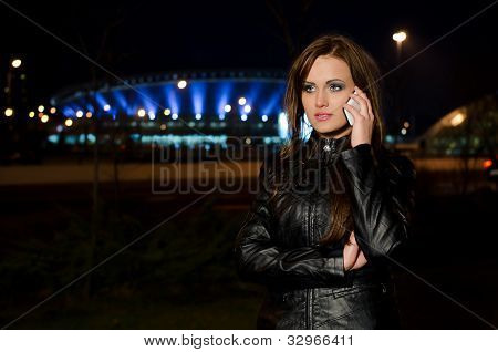 Beautiful Long-haired Woman In A Black Leather Jacket Talking On A Cell Phone
