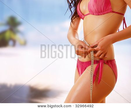 Unknown girl in bikini with tape-measure at sea