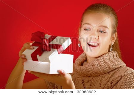 Happy girl opening gift box isolated on red background
